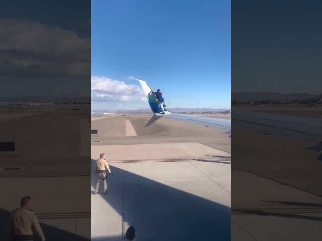 climbing upon the wing of an Alaska Airlines plane set to depart from McCarran International Airport
